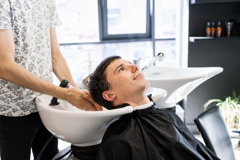 Tvättande hår för frisör till hans stiliga klient Barberare på arbete Man på frisersalongen royaltyfria bilder