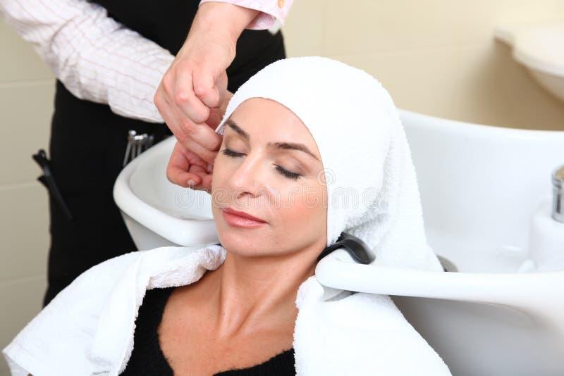 tvättande kvinna för hårpölsalong arkivbild