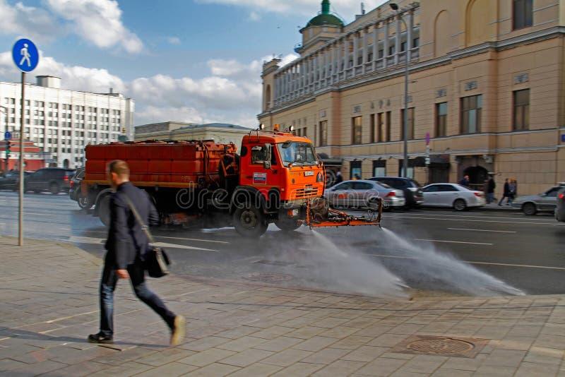 Tvättar det suddiga fotoet för rörelse av att bevattna maskinen den vägdammet och smutsen i Moskva royaltyfri foto