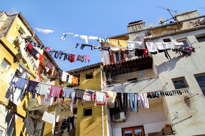 Tvätteri som hänger på en kläderlinje på en gammal byggnad royaltyfria bilder