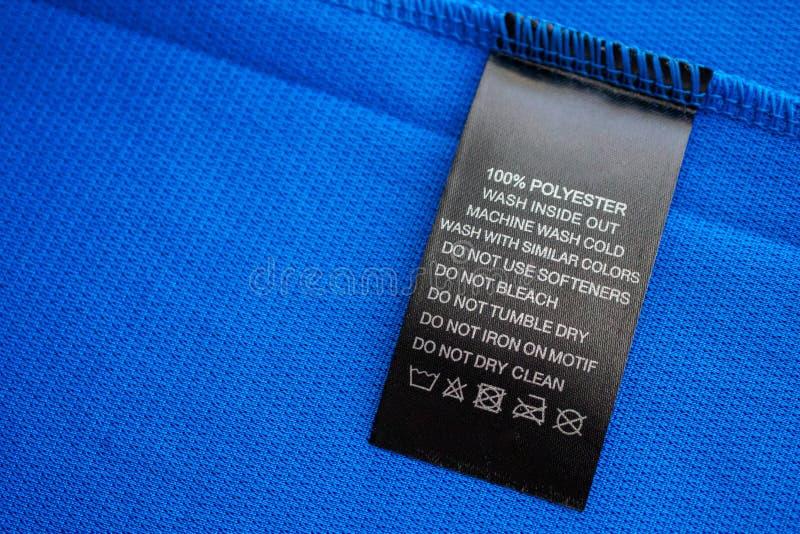 Tvättinstruktioner för svart tvätt etikett på blå tröjor av polyestersportskjorta arkivfoton