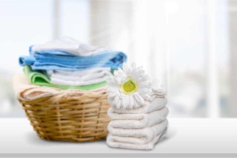 Tvättkorg med färgrika handdukar på bakgrund royaltyfri bild