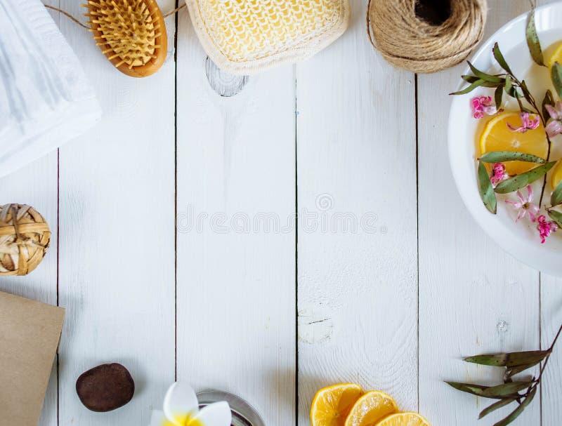 Tvättlapp för handduken för borsten för citronen för det Spa tillbehörbadet blommar på kanterna av fotoet på ett vitt träbakgrund royaltyfria foton