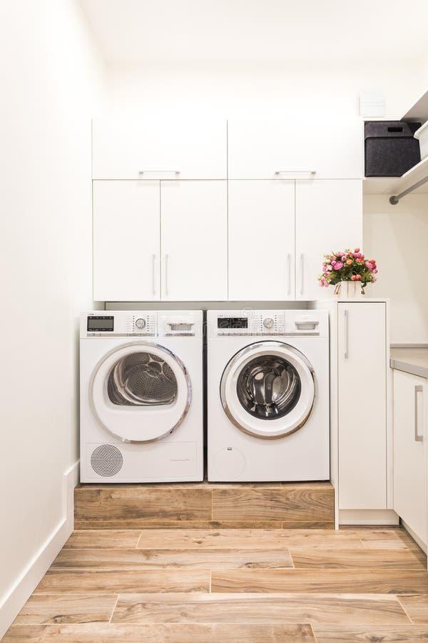 Tvättstuga i modern stil med wasing- och uttorkningmaskinen arkivbilder
