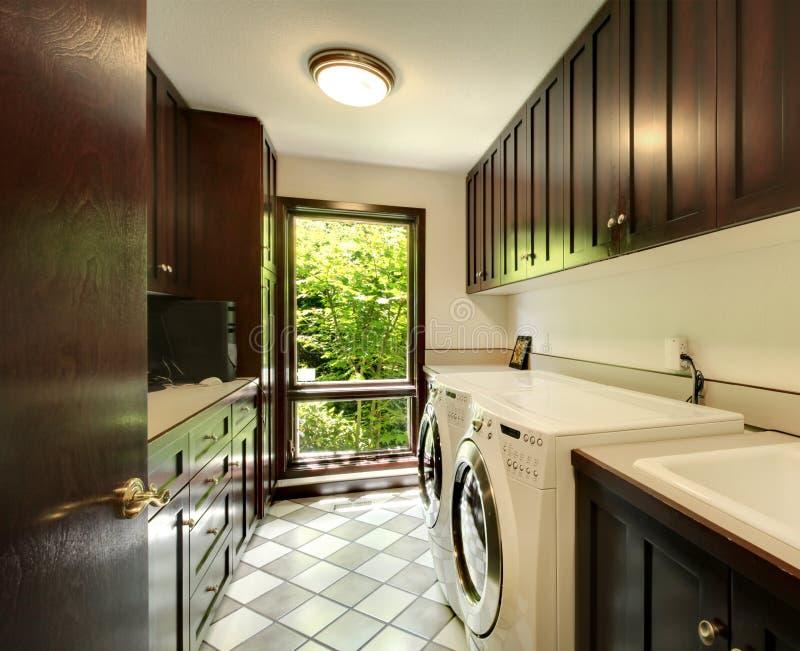 Tvättstuga med wood skåp och vitpackning och tork. arkivfoto