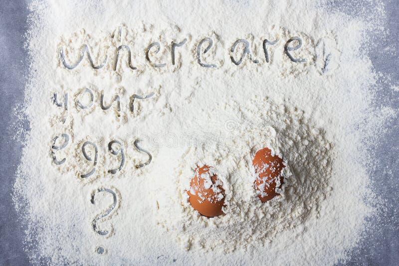 Två ägg i högar av mjöl och orden royaltyfria foton