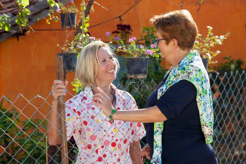 Två äldre damer som pratar i trädgården royaltyfri foto