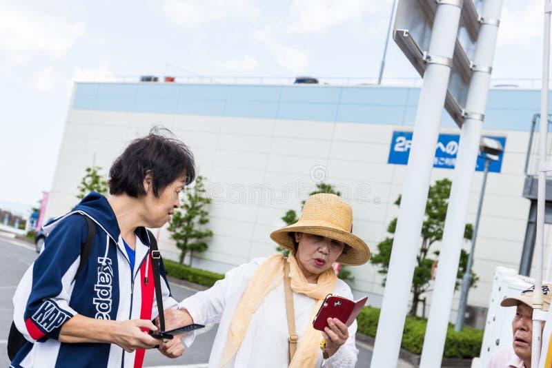 Två äldre japanska damer har gyckel med en smartphone fotografering för bildbyråer