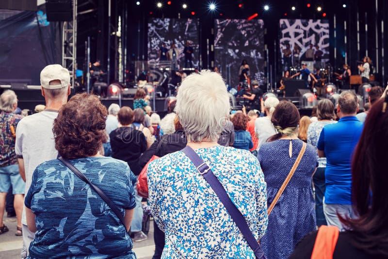 Två äldre kvinnor i folkmassan som lyssnar till gruppen på etappen på en utomhus- musikfestival arkivfoto