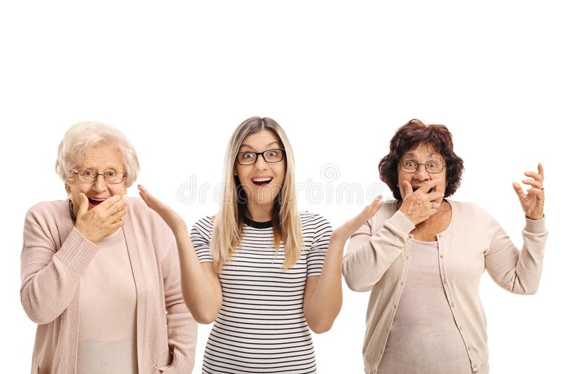Två äldre kvinnor och för en danandeöverraskning för ung kvinna gester arkivbild