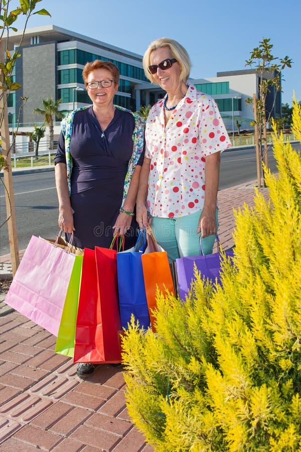 Två äldre kvinnor som shoppar ut royaltyfri foto