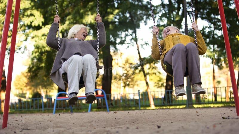 Två äldre kvinnor som skrattar rida gungor parkerar in, äldre vänner, avgång royaltyfria bilder