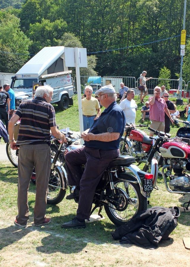 Två äldre män i konversation runt om en tappningmotorcykel på hebden show för medel för brotappninghelg offentlig arkivfoton