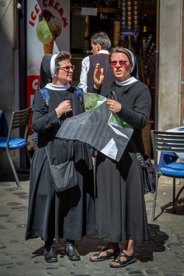 Två äldre nunnor som rymmer en stadsöversikt och till varandra talar royaltyfria bilder