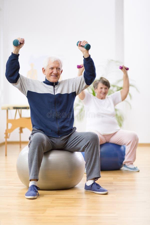 Två äldre patienter som övar med vikter i rehabiliteringmitt royaltyfria foton