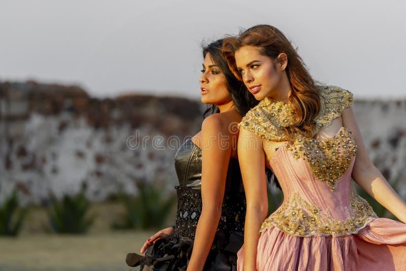 Två älskvärda latinamerikanska brunettmodeller poserar det fria på en mexicansk ranch royaltyfri bild