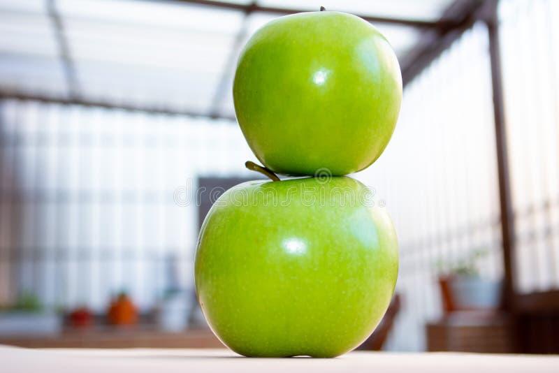 Två äpplen ett överst av det annat slutet upp royaltyfria bilder