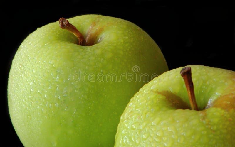 Två äpplen i droppar av vatten arkivbild