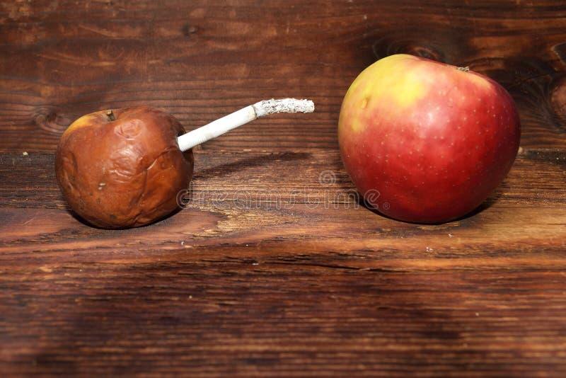 Två äpplen och cigarett i wood bakgrund för byteman för cigarett sjuk rök royaltyfri bild