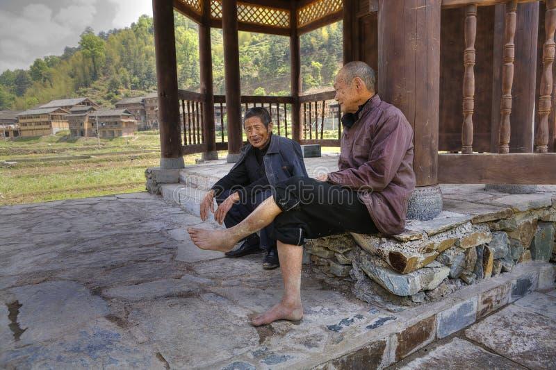 Två åldrades kinesiska män som vilar i skugga under den taklade bron royaltyfri bild