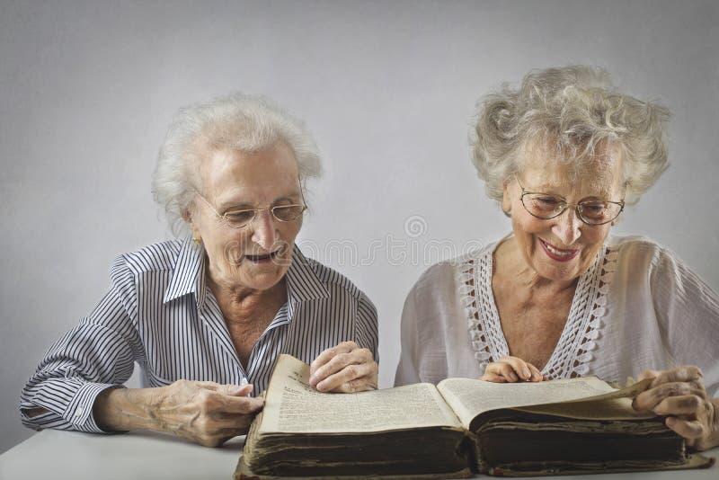 Två åldriga woomen som läser en bok royaltyfria bilder