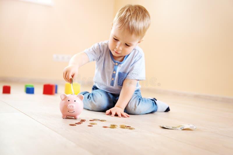 Två år gammalt barnsammanträde på golvet och sättapengarna in i en piggybank royaltyfria foton