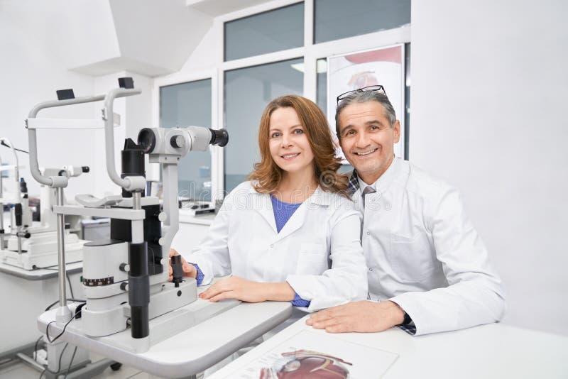 Två ögonläkare som arbetar med den skurna upp lampan i optiskt lager arkivfoto