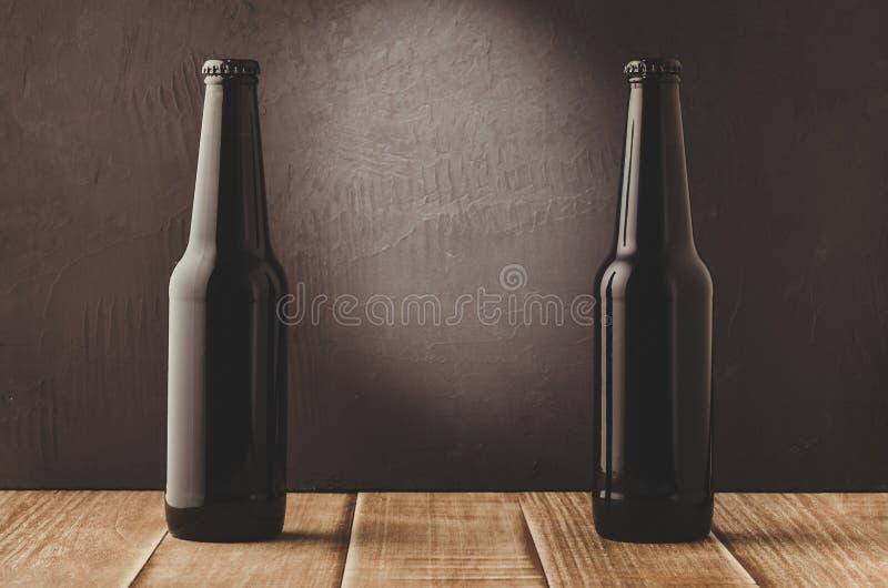 två ölflaskor på en trätabell mot en mörk bakgrund/bla royaltyfri fotografi
