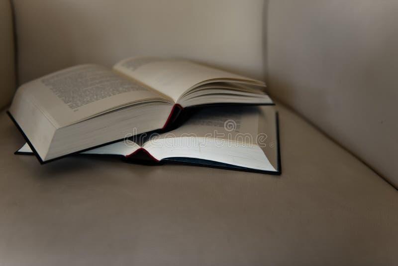 Två öppna böcker på en läderstol royaltyfria bilder