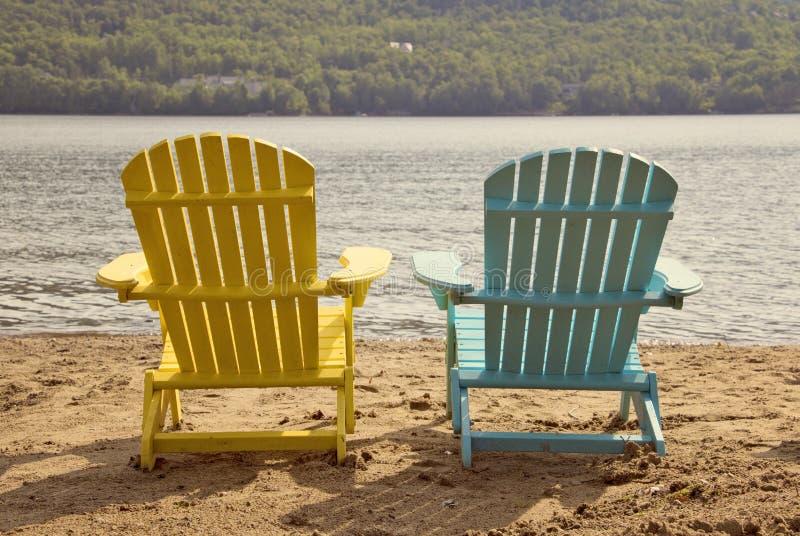 Två adirondackstolar på den sandiga stranden vid sjön royaltyfri fotografi