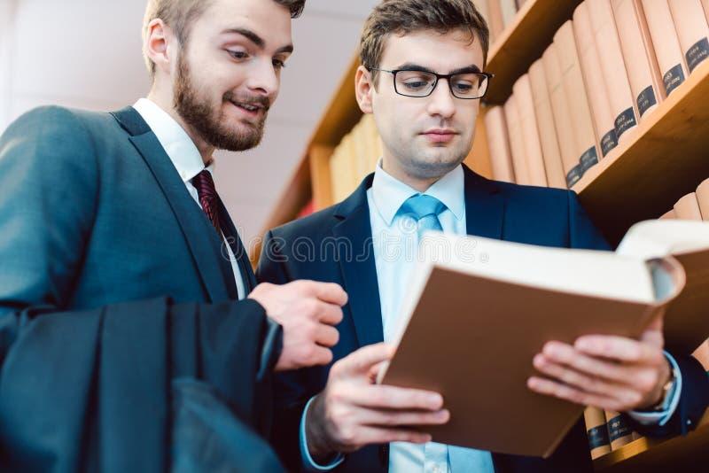 Två advokater i advokatbyrån som diskuterar fall och prejudikat royaltyfria foton