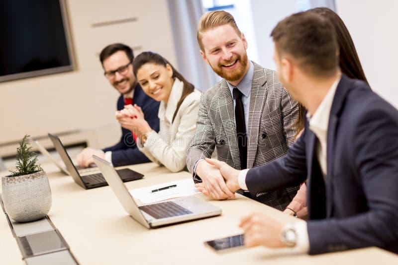Två affärskollegor som skakar händer under möte royaltyfri foto