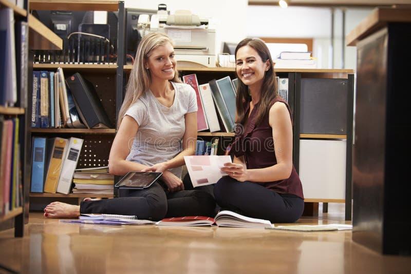 Två affärskvinnaSit On Office Floor With Digital minnestavla arkivfoton