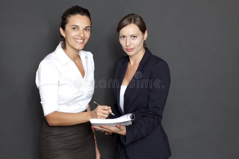 Två affärskvinnor med skrivbordsarbete royaltyfri foto