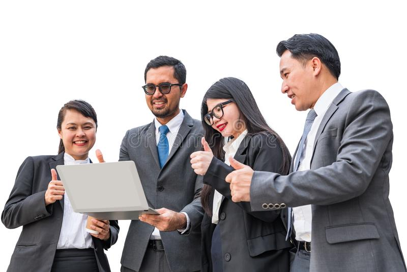 Två affärskvinnor och två affärsmän som ser anteckningsbokdatoren och lyfter upp tummen med att le framsidor royaltyfria bilder