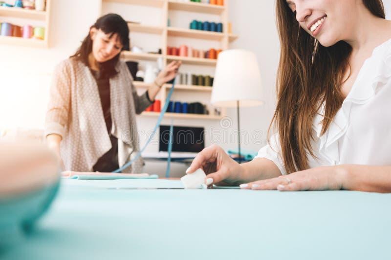 Två affärskvinnor skapar nya kläder för begreppet i sömnadstudio Liten produktion arkivfoto