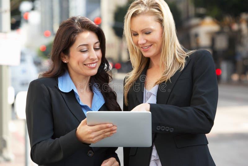 Två affärskvinnor som använder den Digital minnestavlan utanför kontor royaltyfri bild