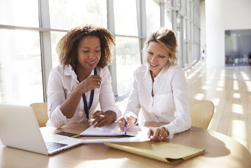 Två affärskvinnor som diskuterar projektet som ner ser arkivfoton