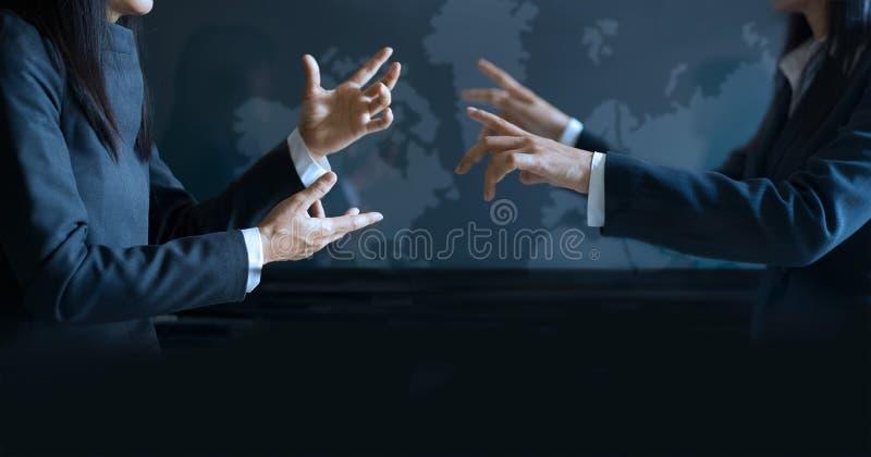 Två affärskvinnor som har talande informellt möte på bakgrund för faktisk skärm royaltyfri bild