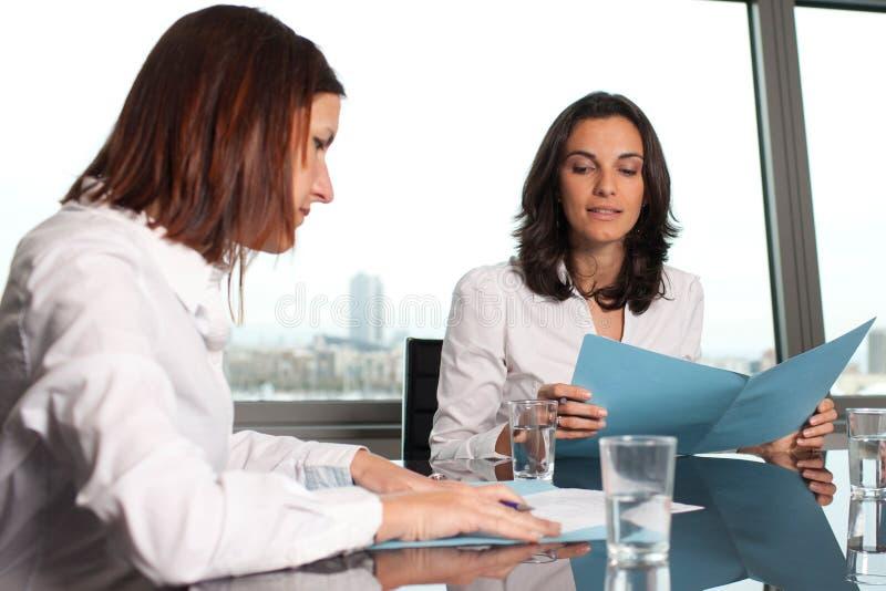 Två affärskvinnor som kontrollerar dokument fotografering för bildbyråer