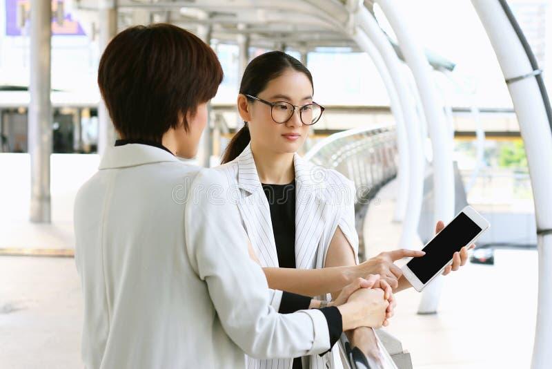 Två affärskvinnor som möter, affärskvinnor som använder minnestavlaPC arkivbild