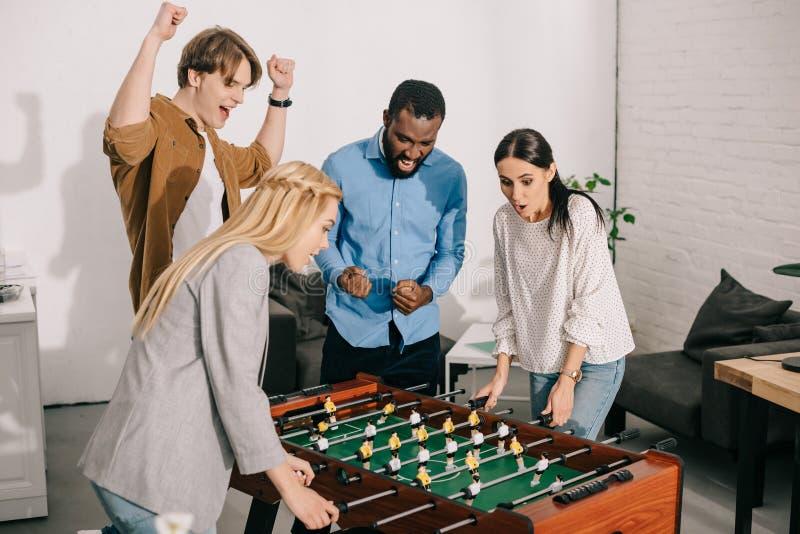 två affärskvinnor som spelar tabellfotboll, och manliga kollegor som hurrar upp dem arkivfoton