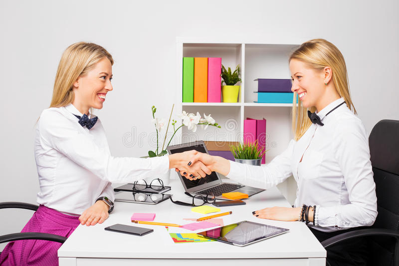 Två affärskvinnor som stänger avtalet med handskakningen arkivfoton