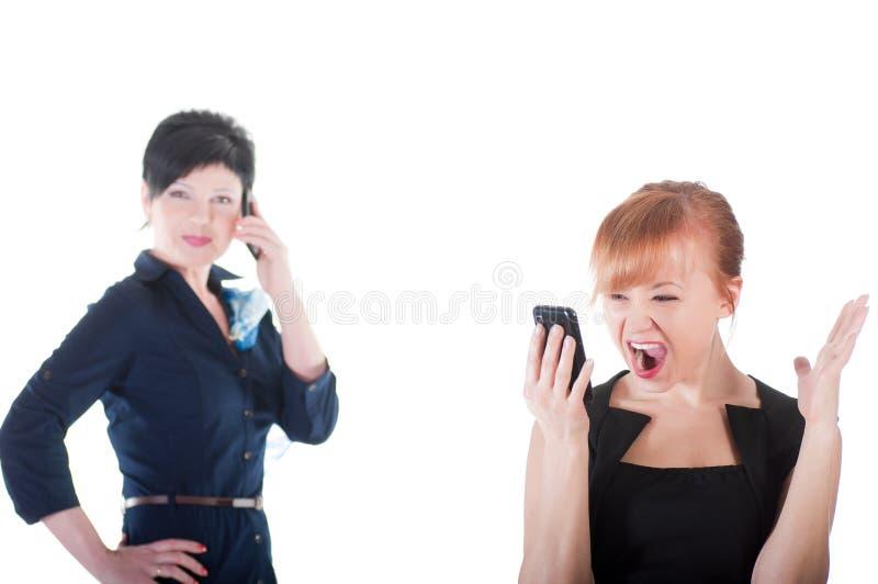 Två affärskvinnor som talar vid mobiltelefoner arkivfoto