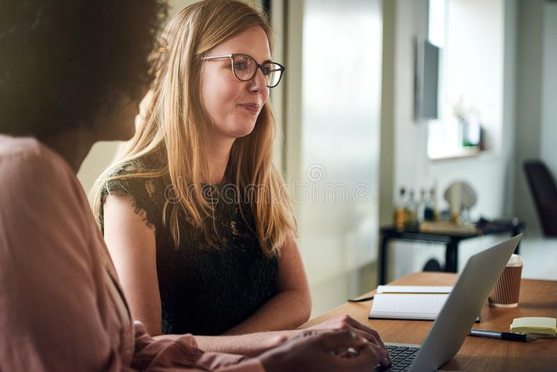 Två affärskvinnor som tillsammans använder en bärbar dator i en kontorsstyrelse fotografering för bildbyråer