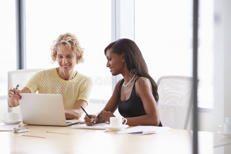Två affärskvinnor som tillsammans arbetar på bärbara datorn i styrelse arkivbilder