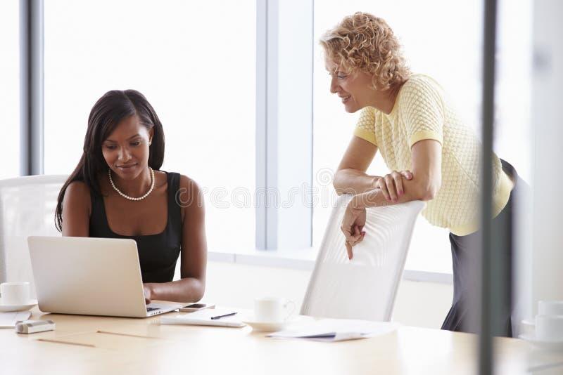 Två affärskvinnor som tillsammans arbetar på bärbara datorn i styrelse arkivfoton