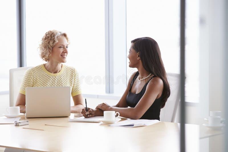 Två affärskvinnor som tillsammans arbetar på bärbara datorn i styrelse royaltyfri foto