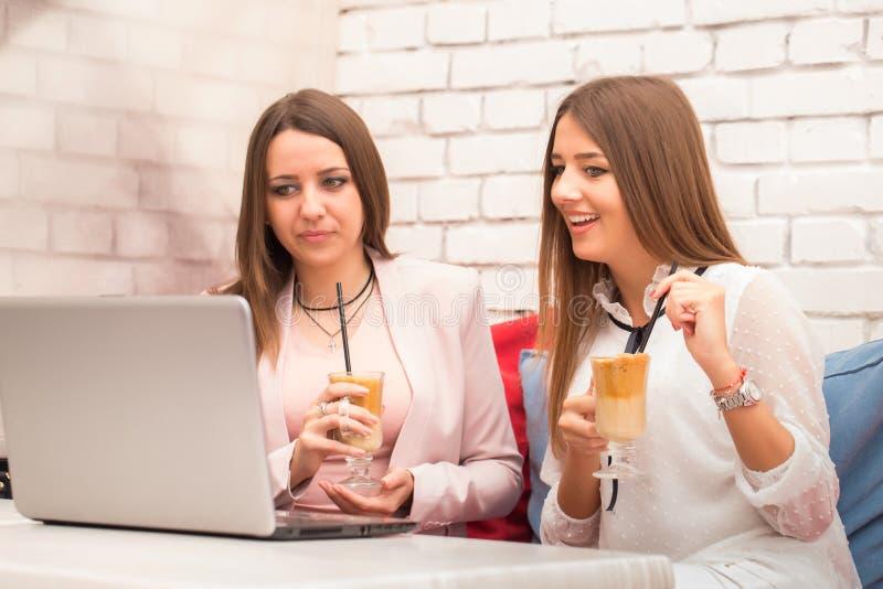 Två affärskvinnor som tillsammans arbetar på en dator i en coffee shop royaltyfria foton