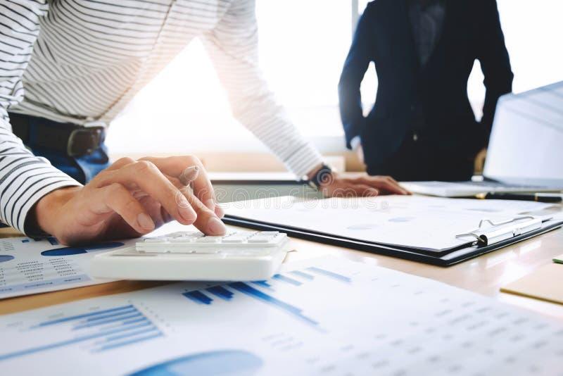 två affärsledare blir partner med analysdatadokumentet med revisorn på kontorsstället arkivfoton